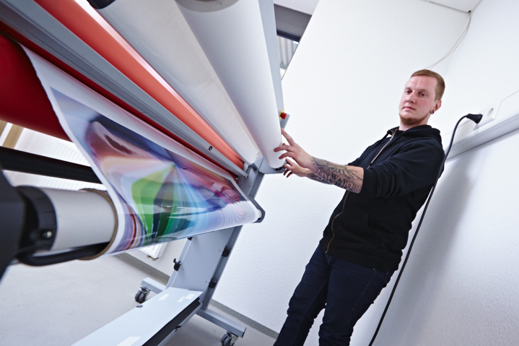 Mitarbeiter kaschiert Digitaldruck mit Schutzlaminat.