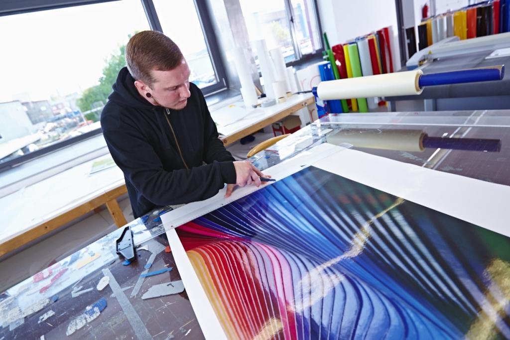 Mitarbeiter schneidet Digitaldruck mittels Messer & Lineal.